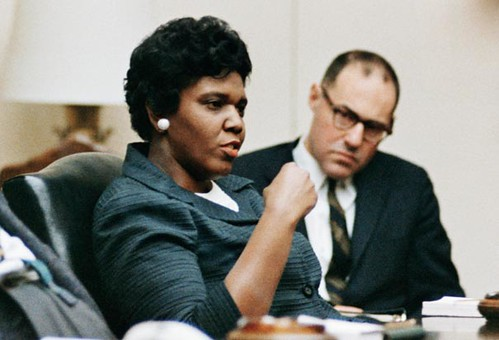a color photograph of Jordan at a meeting. She is speaking. A white man in the background looks on with interest.