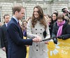 Prince William and Kate Middleton join hands to toss a pancake at a display by the charity Northern Ireland Cancer Fund for Children outside City Hall in Belfast