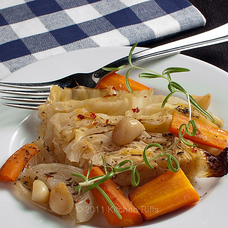braised cabbage with carrots, onions, garlic on plate with fork
