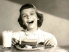 a black and white still of a young white girl smiling strangely in front of her breakfast
