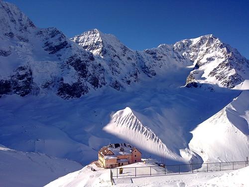 Die verschneite Schaubachhütte mit dem Ortler, dem Zebrù und der Königspitze im Hintergrund