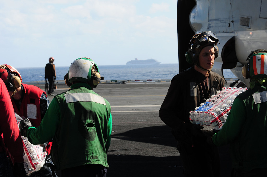 Sailors unload bottles of water for Carnival cruise ship.
