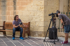 7/52: Lights, camera, action [Explored] (judi may - more off than on) Tags: october2016amonthin31pictures malta valetta street camera tripod cameras wall men people bench fence railings canon7d candid