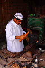 0173 Dubai, UAE (Traveling Man – Back after a long absence) Tags: coffee hammer canon fire iron dubai uae pot arab blacksmith forge unitedarabemirates persiangulf canonef28135mmf3556isusm heritagevillage 50d southwestasia arabianpeninsula alshindagha canoneos50d markaveritt traditionalblacksmith