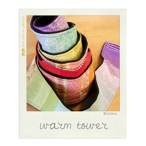 A rainbow patchwork strip pieced scarf with black fleece backing