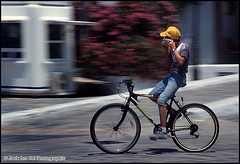"""Houston, are you receiving?"" - 1997 (Jack the Hat Photographic) Tags: street boy man blur film bike bicycle yellow radio 35mm island greek mediterranean fuji ride candid fast kos greece riding listening cap biker panning walkietalkie sensia nohands jamierobertson jackthehat"
