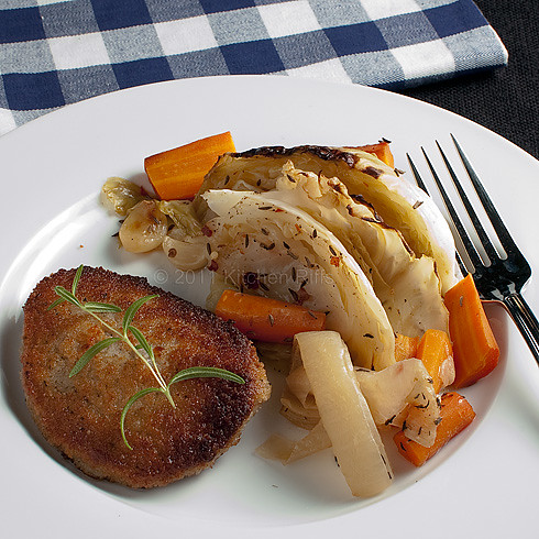 bread veal patty on plate with braised cabbage with carrots, onions, and garlic