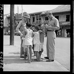 Filipino children make friends with two Naval officers in downtown Manila, hoping for a gift in return., 05/1945 (The U.S. National Archives) Tags: boy boys children philippines wwii worldwarii manila soldiers pto khakis nationalarchives secondworldwar worldwartwo pithhelmet pacifictheatre pacifictheater pacifictheaterofoperations pacifictheatreofoperations nara:arcid=520951