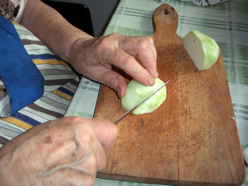 A grandmother chopping a vegetable in the kitchen