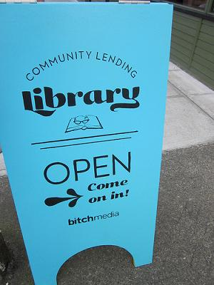 A photo of the Bitch Community Lending Library's sandwich board. It's teal with black print that reads Community Lending Library above an image of an open book with glasses on top. Below the image, the sign reads OPEN Come on in! with an arrow pointing to the left