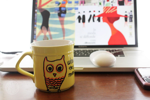 Owl cup sitting in front of a laptop