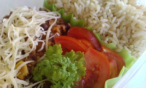 Een simpele plastic doos, tot een-derde gevuld met zilvervliesrijst (rechts). Tegen de rijst is er siliconen baran die er uit ziet als slablaadjes. Rechtsonder in de overgebleven ruimte liggen 6 halve plakjes tomaat met wat krulpeterselie. De rest is gevuld met een chili met fijngeraspte belegen kaas. De chili is op tomatenbasis en je kunt stukjes gebraden gehakt, gesneden ui, maïskorrels en kidneybonen zien.