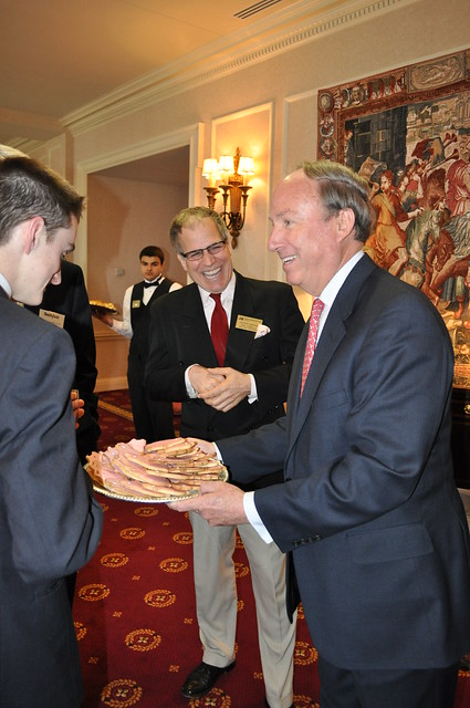 CNU President Paul Trible hands out pig-shaped cookies to participants of CNU's President's Leadership Program
