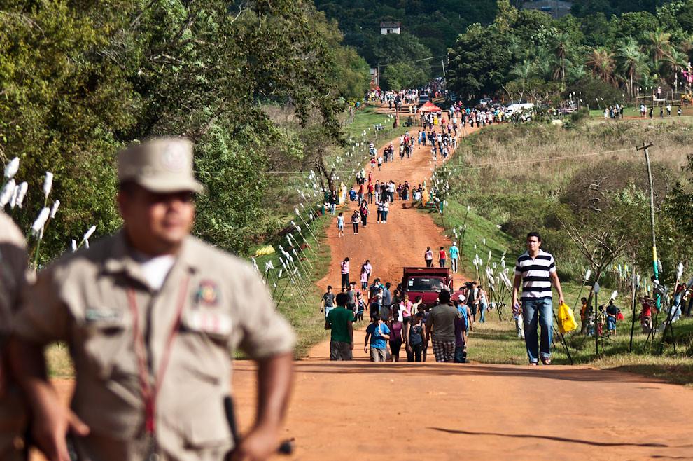 Un policía controla la seguridad y desvía el trafico de vehículos en la polvorienta calle principal del pueblo. A pocas horas del comienzo de la marcha se bloquean los accesos para vehículos de tal forma que se garantice el espacio y la seguridad para una asistencia masiva de aproximadamente 15 mil personas. (Elton Núñez - San Ignacio, Paraguay)