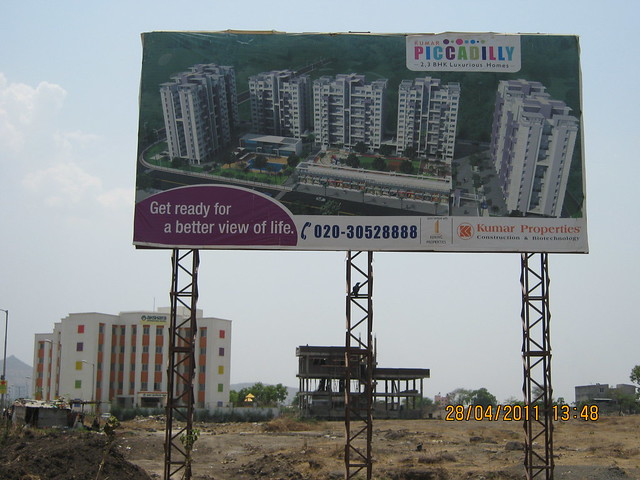 Hoarding of Kumar Piccadilly 2 BHK 3 BHK Flats opposite Akshara International School Wakad Pune