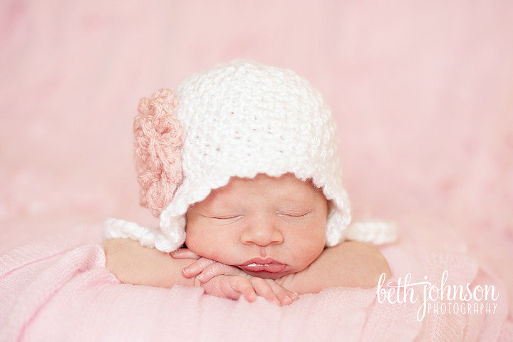 newborn baby girl in white hat on pink ruffled blanket