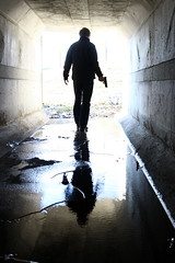 ice water in his veins (FotoFiction For Book Covers) Tags: light shadow urban usa man reflection male film ice water silhouette mystery modern danger standing dark walking concrete outdoors virginia gun alone adult action threatening dramatic tunnel story criminal crime killer weapon pistol spy only murder lone highkey backlit cinematic anonymous threat oneperson culvert backview jamesbond assassin detective thriller lonefigure