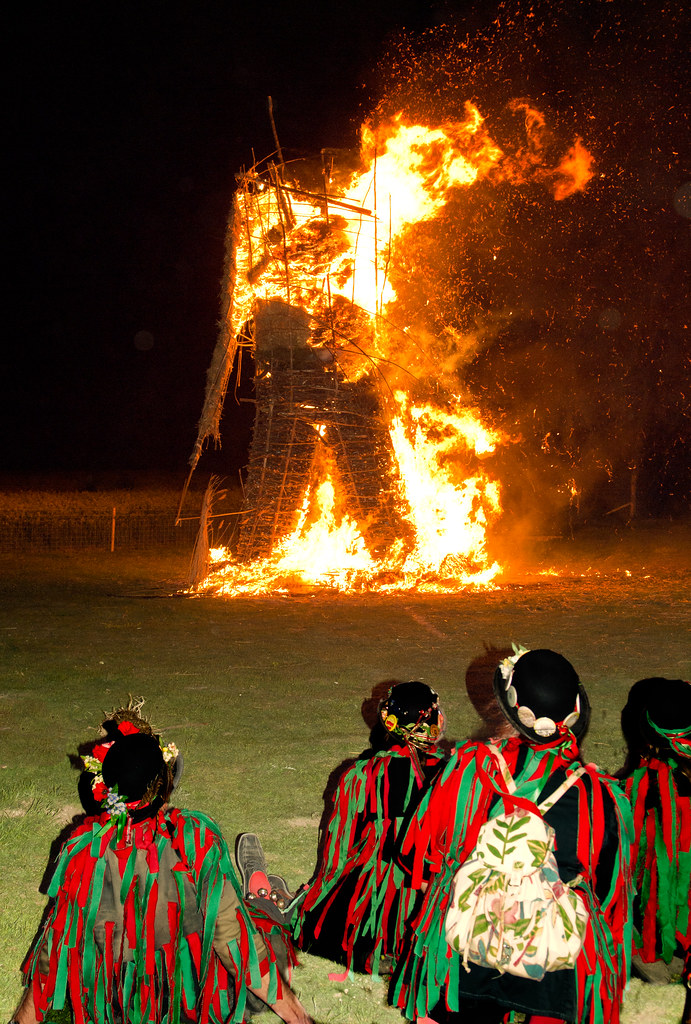 Morris dancers in traditional costume  watch the burning of the Wicker Man at  the 2011 Beltain festival held at Butser Ancient Farm