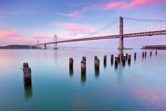 The Promises of Springtime (Jared Ropelato) Tags: sanfrancisco california city longexposure trip travel bridge sunset vacation sky urban nature water beautiful clouds canon landscape lights bay site spring francisco day pacific outdoor tripod scenic illumination visit scene adventure clear trail filter embarcadero pylons rugged illuminate manfrotto lansdscape giotto pilon cablerelease 2011 1635mm singhray 5dmkii jaredropelato ropelatophotography