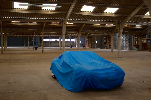 Car under cover in empty warehouse