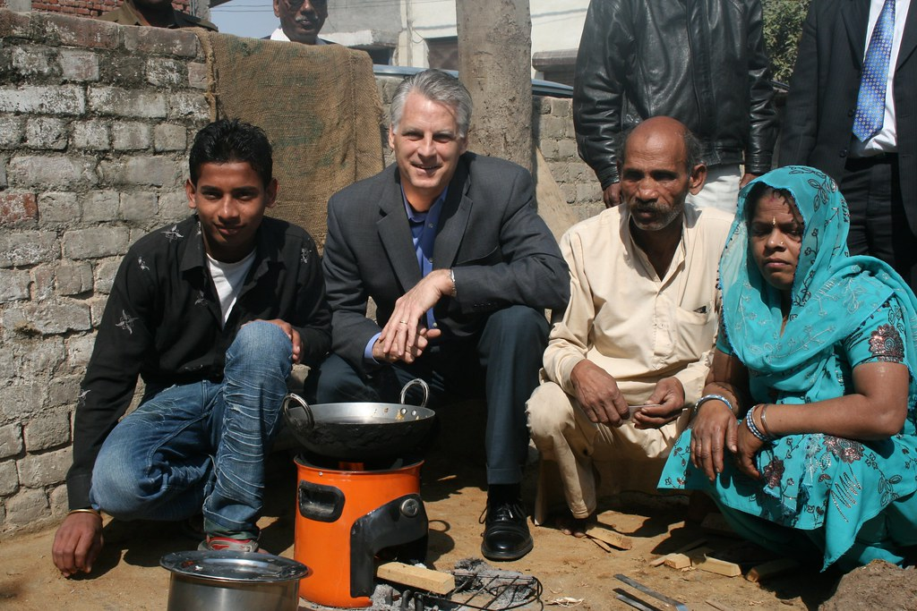 Ambassador Roemer with a family in Sonia Vihar that switched to the Envirofit cook stove