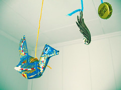 hanging in my room 1 (incompletethoughts) Tags: origami colorful yarn string foundobjects bottlecap pendant origamibird
