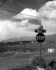 01481-Vegas and Main-1 (Jim There's things half in shadow and in light) Tags: road travel vegas blackandwhite tourism sign clouds tour desert nevada main sightseeing tourist stopsign sandscape goodsprings ilobsterit