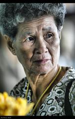 Woman (Polis Poliviou) Tags: flowers portrait woman face yellow lady canon thailand eos asia market head thai chiangmai oldwoman chiangrai polis agedwoman afiap poliviou polispoliviou fantasticthailand artistefiap   allrightsreservedbypolispoliviou