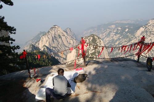 In der Nähe des Westgipfels vom Hua Shan richtet ein Maler seine Papier aus. Die roten Schleifen sind an Vorhängeschlössern angebracht und sollen den Besuchern Glück bringen