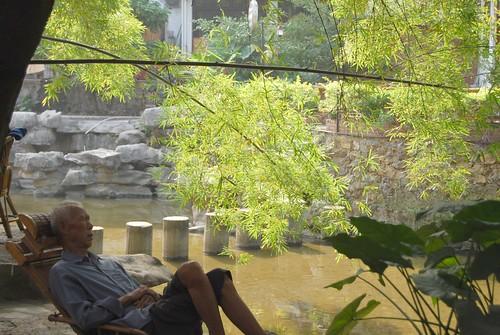 Zur Mittagszeit schläft ein alter Chinese im Liegestuhl am Bachufer unter einem Baum und vor einem Blatt.