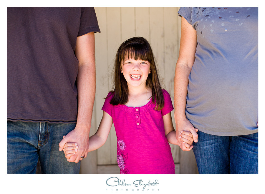 little girl holding parents hands