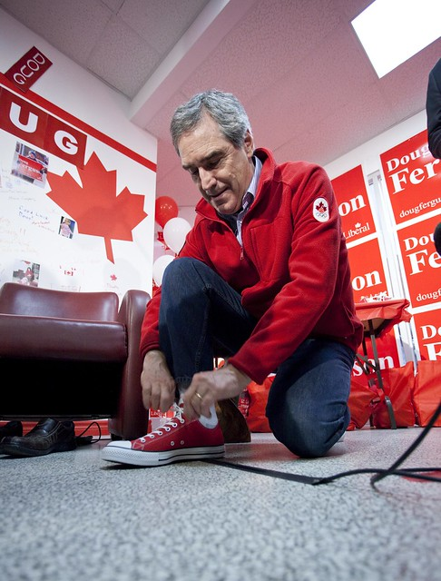 Michael Ignatieff laces up a pair of red sneakers in Doug Ferguson's campaign office. Photo: Georges Alexandar