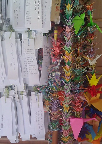 Strings of origami cranes, and hundreds of prayers on white paper at the Earthquake Victims Memorial in the Japanese Garden