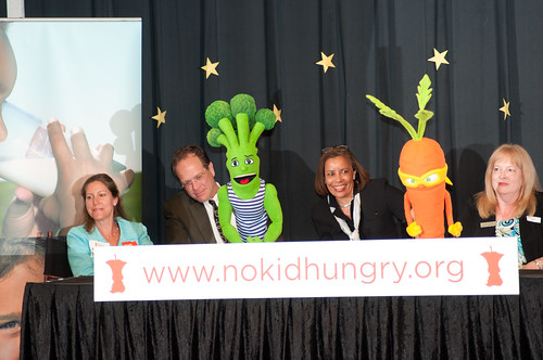 Left to right on stage, School Board Vice Chairperson Abby Raphael, Arlington County School Superintendent Patrick K. Murphy, Federation of Virginia Food Banks Executive Director Leslie Van Horn, Barcroft Elementary School Principal Miriam Hughey-Guy, as two of the Super Sprowtz super-powerful vegetable super hero puppet characters, Brian Broccoli and Colby Carrot, encourage the students, parents and teachers of Barcroft Elementary School to get up and dance, during the launch of the Virginia No Kid Hungry Campaign at the Arlington, VA, school on Tuesday, June 7, 2011. USDA Photo by Lance Cheung.