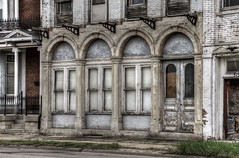 Streetside elegance in deep decline (Lights in my hometown) Tags: old windows building abandoned architecture highway peeling paint doors decay style arches iowa sidewalk forgotten weathered fading roadside derelict deserted dilapidated leecounty elegance arched fortmadison us61