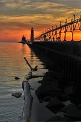 Michigan's West Coast (Robby Ryke) Tags: longexposure sunset sun lighthouse sol colors yellow pier rocks michigan grandhaven