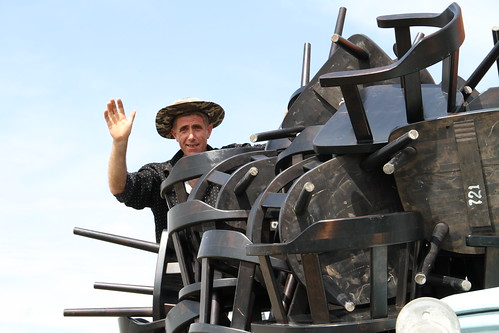 man stacking chairs on an old Soviet truck