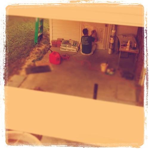 Dad sanding the shed door.