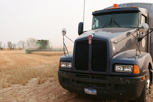 One of our trucks parked at the end of the field with a combine in the background.