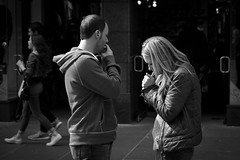 A Spark Between Them (Leanne Boulton) Tags: life lighting street city light shadow two portrait people urban blackandwhite bw woman sunlight white man black detail male texture girl monochrome beautiful beauty modern female standing canon hair 50mm mono living blackwhite store hoodie aperture focus couple pretty shadows adult natural habit humanity bokeh outdoor pavement glasgow cigarette candid smoke pair group young streetphotography documentary style social scene highlights smoking doorway health human shade 7d blonde bandw smoker issue addiction depth tone interaction candidstreetphotography