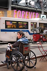 FOREVER (fotophriendly) Tags: nyc newyorkcity pink red motion bus bike composition person hit doll poetry wheelchair wheels americanflag american timessquare forever handicap powerful newyorknewyork mosca poignant thebigapple thoughtprovoking nycwalkabouts supershot ©allrightsreserved photographicexcellence amomentarylapseofreason mycameraneverlies heartawards canon40d picturesworthathousandwords picturesfromnewyorkcity photographersgonewild fotophriendly artofimages flickrunitedaward rchommel poppyawards youcallitartwhynot presslforlargeonblack coolhairlikemyidolwarhol panemetcircensesbreadandcircuses orroriedeliriurbaniurbanhorrors