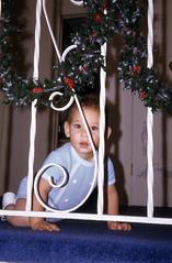 Bobby peering through the hallway railing (epicharmus) Tags: christmas boy ny newyork 1969 carpet hall kid toddler child wroughtiron suburbia garland holly longisland hallway suburbs suburb kodachrome railing crawling christmastime colorslide artificialplant 35mmslide nassaucounty daddino northbellmore robertdaddino processedjanuary1970