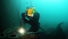 Navy Diver 2nd Class Ryan Arnold welds a patch onto an underwater structure.