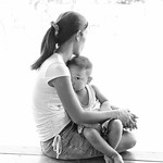 Carer and child at a local school waiting for an older sibling to come home. Taken in Northern Thailand.