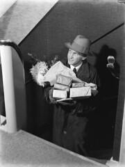 Man met handen vol pakjes / Man carrying wrapp...