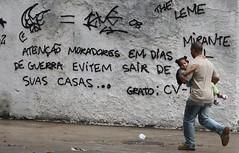 Morador protegendo sua filha durante tiroteio / Foto: Domingos Peixoto