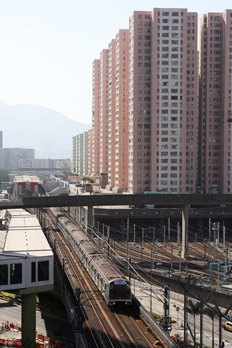 Train departs Kowloon Bay station, Kowloon Bay depot is located alongside, under the Telford Garden housing estate