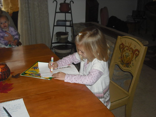 Five year old Hannah Yorgey draws at the table.