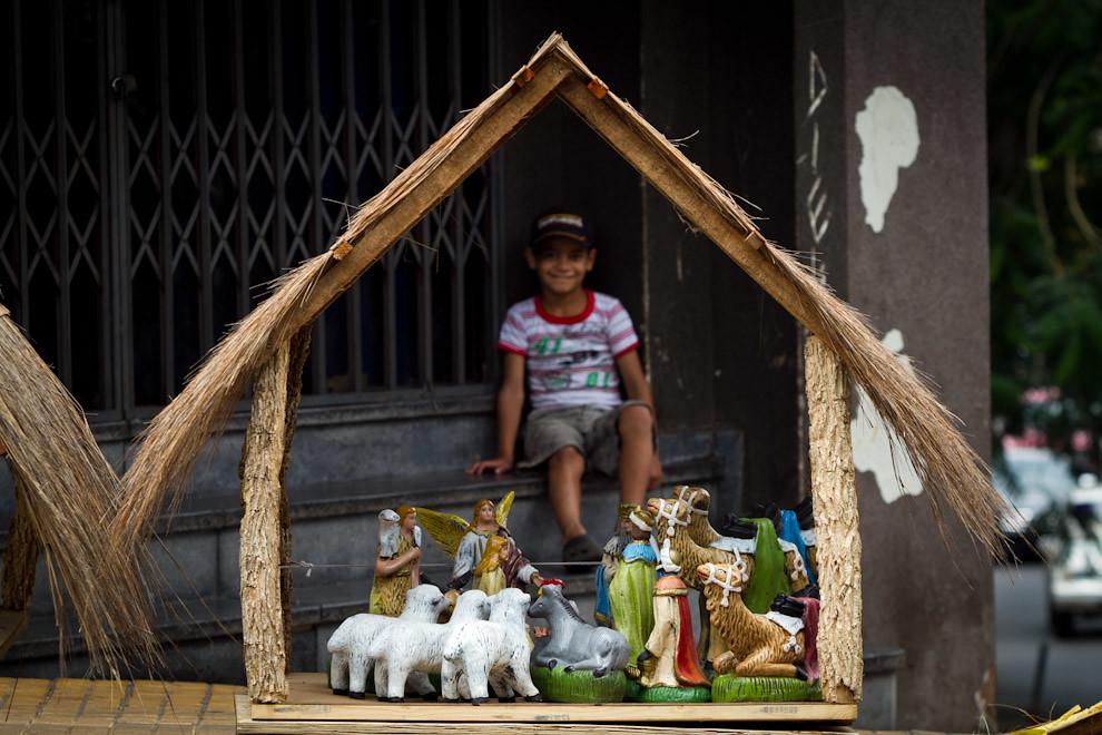 La típica choza con  paja que representa al pesebre, es ofrecida para su venta por este niño, en  una concurrida esquina del Mercado 4. (Tetsu  Espósito - Asunción, Paraguay)