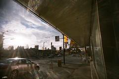 lens flare of sun (SqueakyMarmot) Tags: urban vancouver toycamera 35mmfilm lensflare dairyqueen neighbourhood plasticcamera crepuscularray easthastingsstreet vivitarultrawideslim grandviewwoodlands fujifilms200